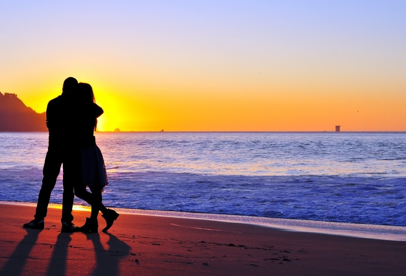 happy, 2-silhouette-of-couple-embracing-on-beach-at-sunset