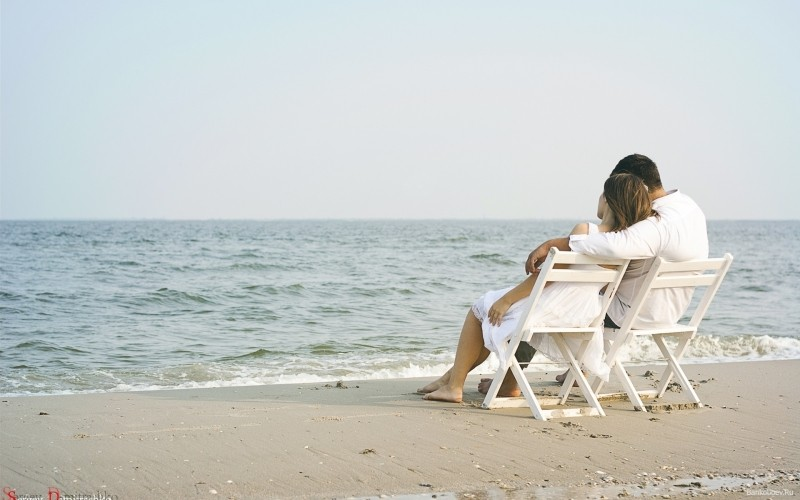 2-young-couple-embracing-on-beach-and-looking-at-sea