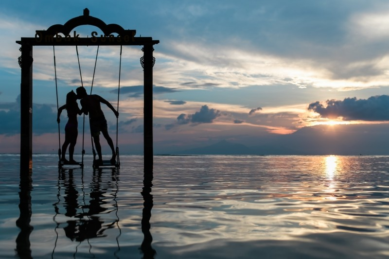 happy,silhouette-of-young-couple-kissing-on-swing-at-sunset