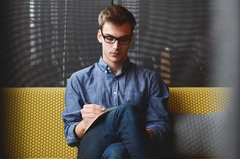 1-young-man-sitting-on-sofa-and-writing-in-notebook