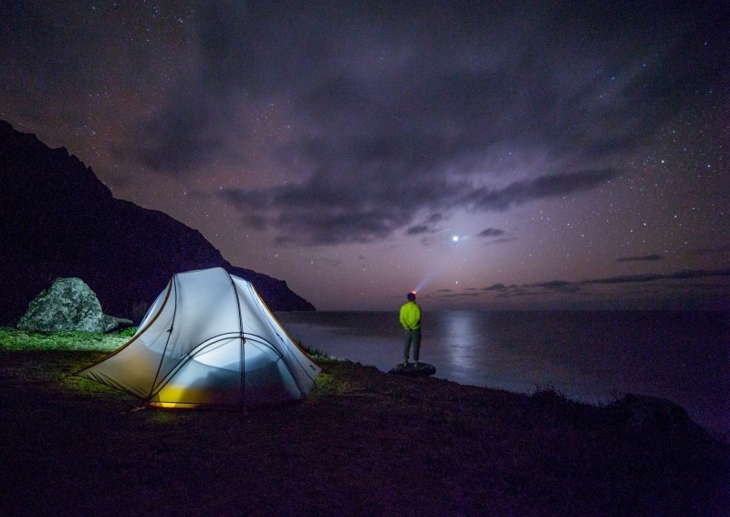 2-stars-in-night-sky-admired-by-tourist-on-rock
