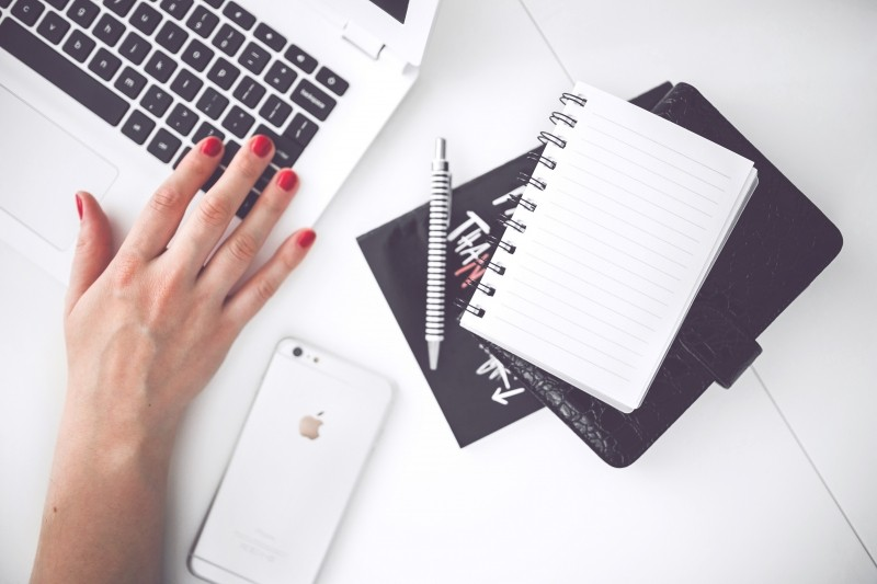 woman-working-on-laptop-with-notebook-and-mobile-phone-on-table