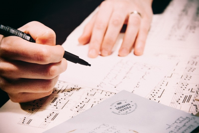 man-writing-letter-on-music-sheet