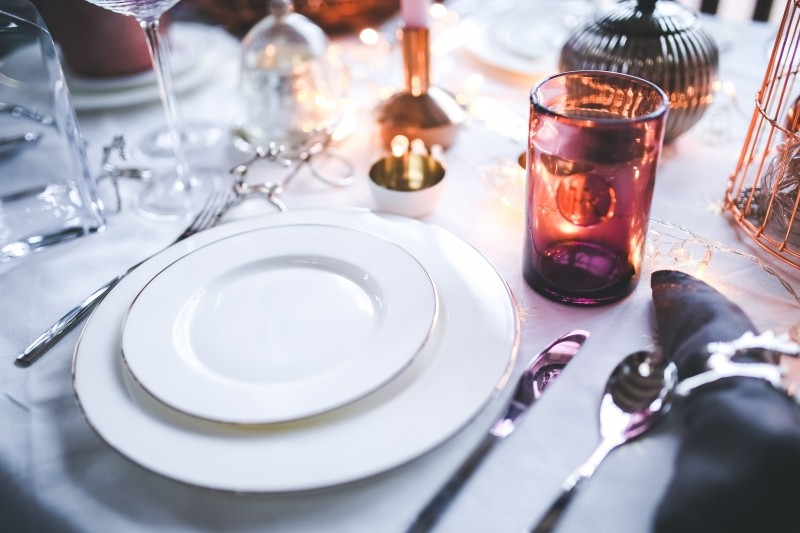elegant-table-with-plates-and-glasses-on-white-tablecloth