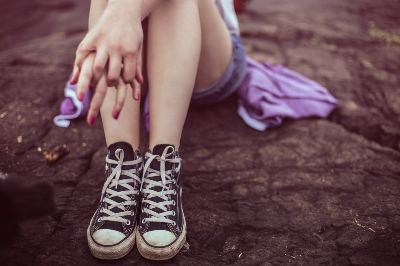 girl-wearing-canvas-shoes-and-sitting-on-rock