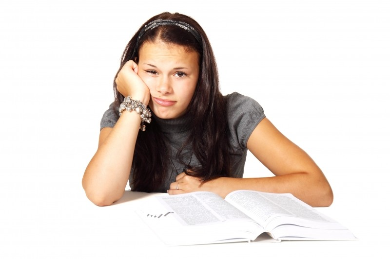 young-woman-sitting-at-table-with-open-book