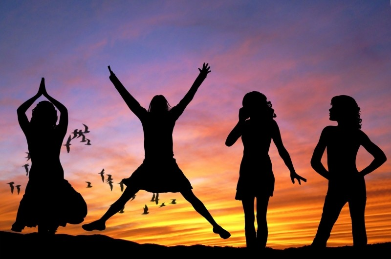 happy, silhouette-of-female-friends-relaxing-at-sunset-with-birds-in-background