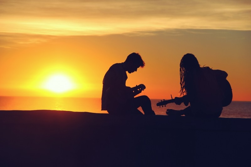 happy, silhouette-of-young-couple-playing-guitar-at-sunset