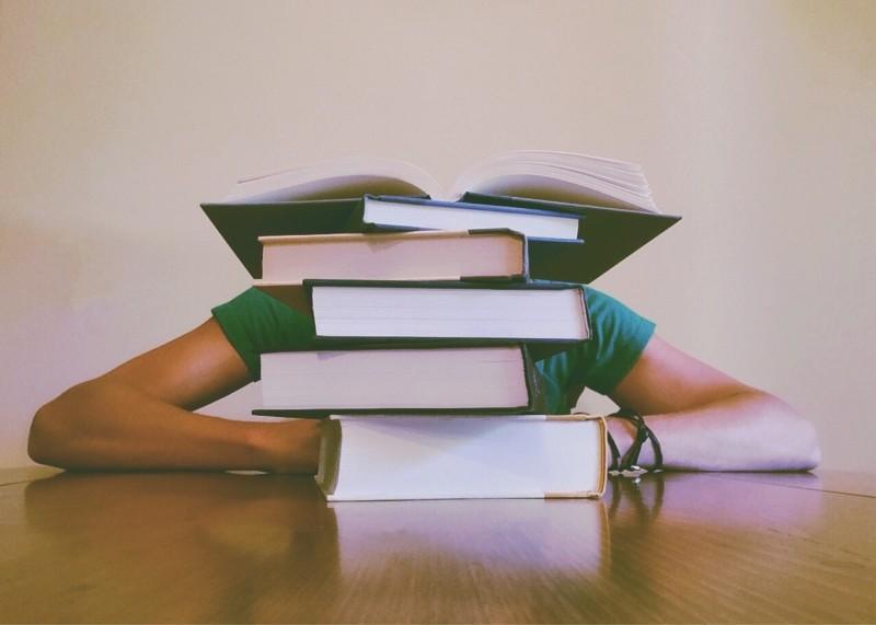 study, man-sitting-behind-pile-of-books